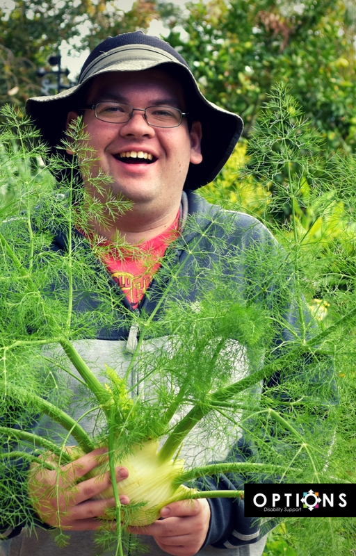 man holding fennel in lush Edible Garden
