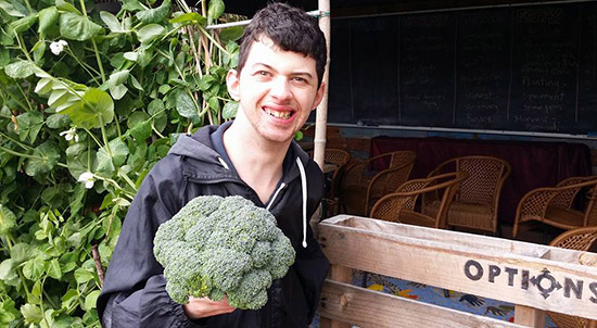 Man standing in Edible Garden holding a big head of broccolli
