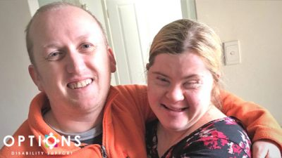 Married couple, with disabilities hugging and smiling