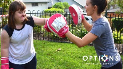 woman boxing with fitness trainer