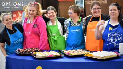 Group of adults wearing colourful aprons selling cakes for Australia's Biggest Morning Tea